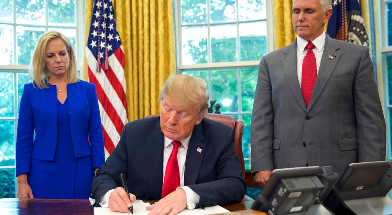 President Donald Trump signs an executive order to keep families together at the border, but says that the 'zero-tolerance' prosecution policy will continue, during an event in the Oval Office of the White House.