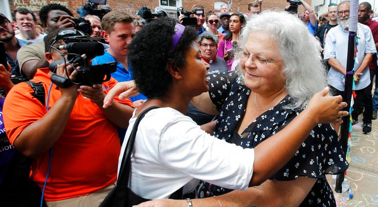 Susan Bro, right, mother of Heather Heyer who was killed during last year's Unite the Right rally, embraces a supporter after laying flowers at the spot her daughter was killed in Charlottesville, Va., Sunday, Aug. 12, 2018.