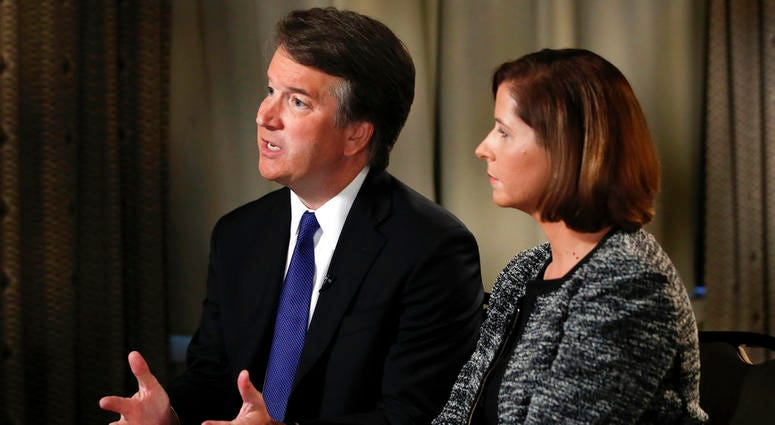 Brett Kavanaugh, with his wife Ashley Estes Kavanaugh, answers questions during a FOX News interview, Monday, Sept. 24, 2018, in Washington, about allegations of sexual misconduct against the Supreme Court nominee