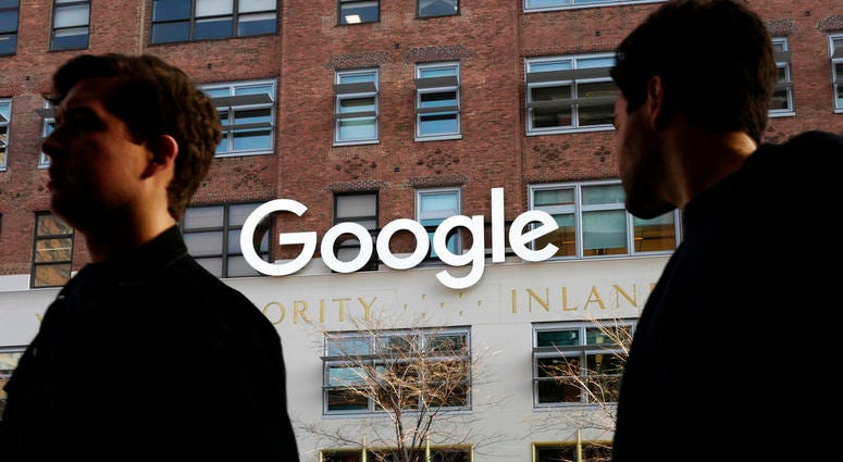 In this Dec. 4, 2017 file photo, people walk by Google offices in New York.