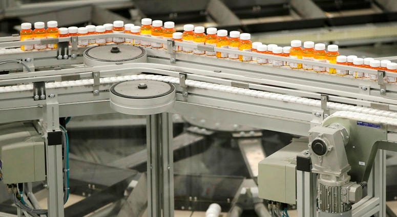 FILE- In this July 10, 2018, file photo bottles of medicine ride on a belt at the Express Scripts mail-in pharmacy warehouse in Florence, N.J.