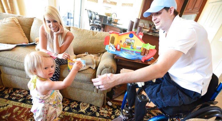 In this AprIl 1, 2015, file photo, retired Air Force Airman Brian Kolfage, right, gives a piece of cheese to his 1-year-old daughter Paris Kolfage as his wife Ashley Kolfage looks on at their recently rented home in Sandestin, Fla.