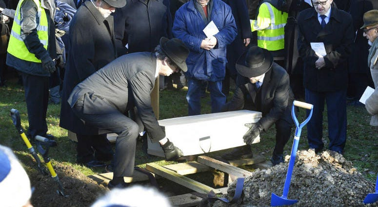 A coffin with the remains of six unidentified Holocaust victims is buried at the United Synagogue's New Cemetery in Bushey, England, Sunday Jan. 20, 2019.
