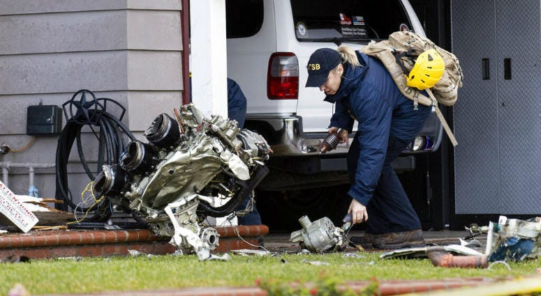 A National Transportation Safety Board worker takes a photo of an engine that came to rest against a house on Crestknoll Dr. in Yorba Linda, Calif on Monday, February 4, 2019.