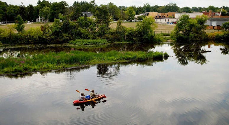 ILE- In this Aug. 14, 2017 file photo, a couple kayak on the Rogue River adjacent to where Wolverine World Wide's tannery once stood, in Rockford, Mich.