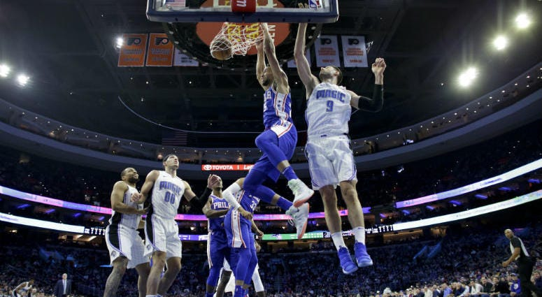 Philadelphia 76ers' Ben Simmons, center, dunks the ball past Orlando Magic's Nikola Vucevic, right, during the first half of an NBA basketball game, Tuesday, March 5, 2019, in Philadelphia.