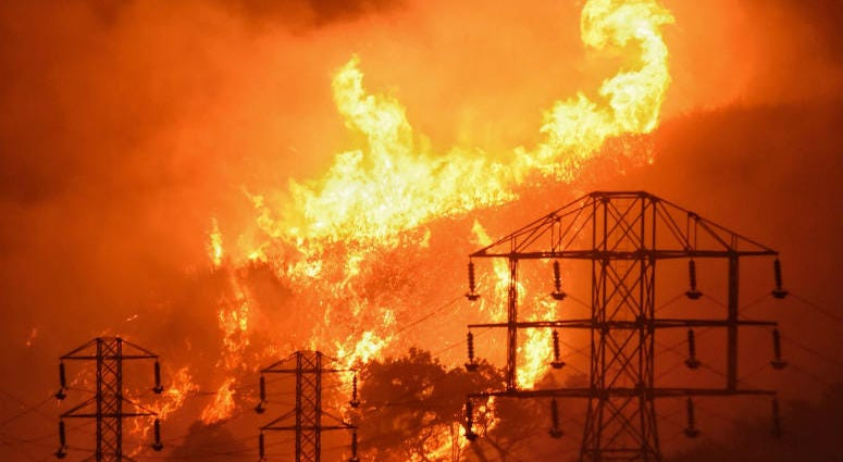 FILE - In this Dec. 16, 2017, file photo provided by the Santa Barbara County Fire Department, flames burn near power lines in Sycamore Canyon near West Mountain Drive in Montecito, Calif.