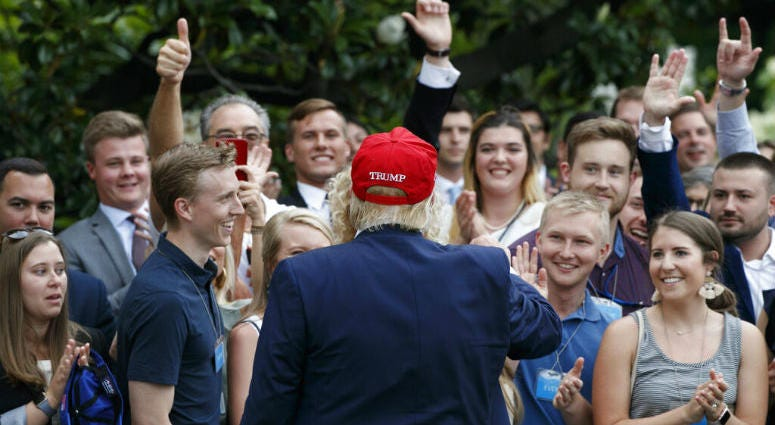 President Donald Trump greets supporters on his return to the White House, Friday June 7, 2019, in Washington.