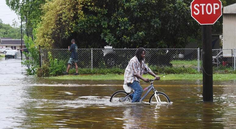 A man tries to bike through the flooding from the rains of storm Barry on LA Hwy 675 in New Iberia, La., Sunday, July 14, 2019.