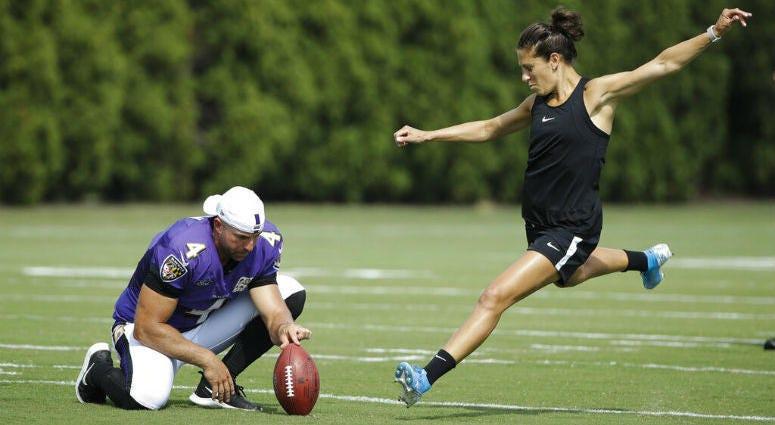 Baltimore Ravens' Sam Koch holds the ball for United States soccer player Carli Lloyd as she attempts to kick a field goal after the Philadelphia Eagles and the Baltimore Ravens held a joint NFL football practice in Philadelphia, Tuesday, Aug. 20, 2019.