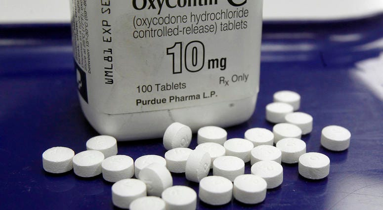 Aa pharmacist in San Francisco poses for photos holding a bottle of OxyContin.