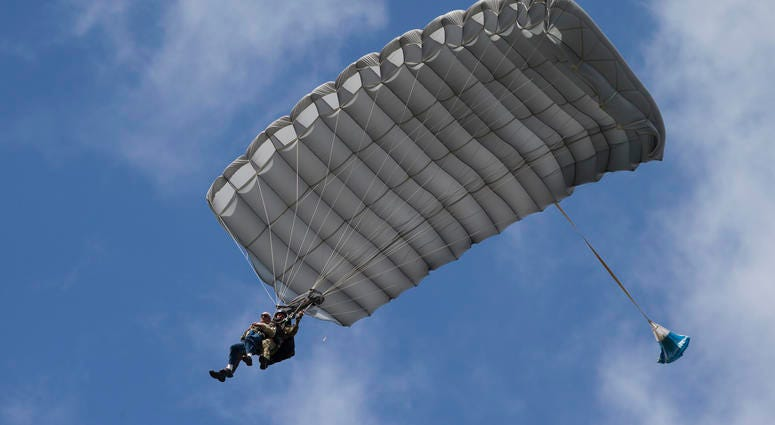 Tom Rice, a 98-year-old American WWII veteran, front left, approaches the landing zone during a tandem parachute jump near Groesbeek, Netherlands, Thursday, Sept. 19, 2019.