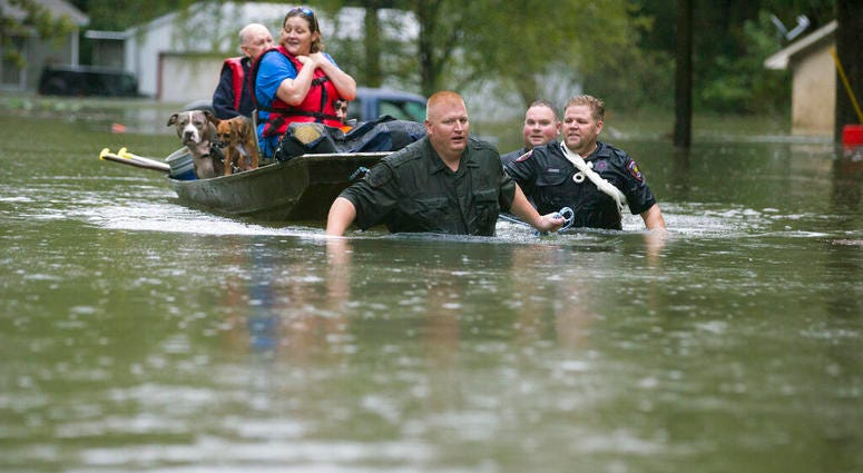 Splendora Police Lt. Troy Teller, left, Cpl. Jacob Rutherford and Mike Jones pull a boat carrying Anita McFadden and Fred Stewart from their flooded neighborhood inundated by rain from Tropical Depression Imelda.
