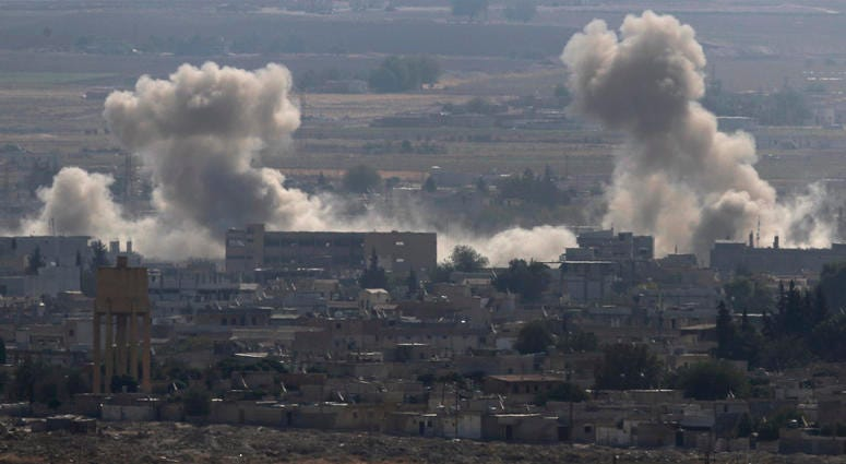 Sanliurfa province, southeastern Turkey, smoke and dust billows from targets in Ras al-Ayn, Syria, caused by bombardment by Turkish forces, Tuesday, Oct. 15, 2019.