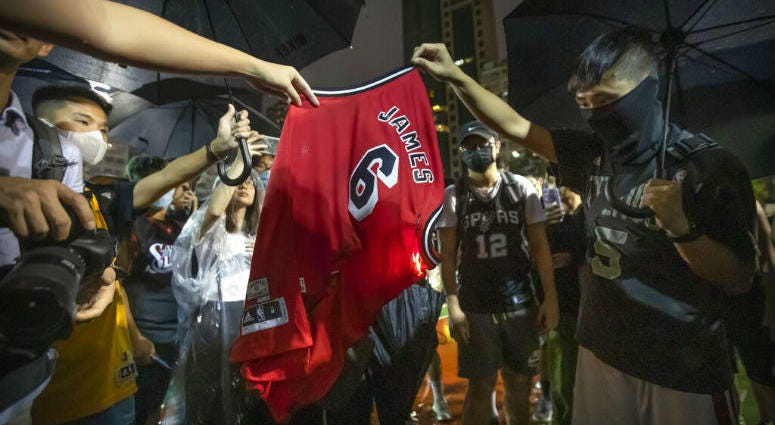 Demonstrators set a Lebron James jersey on fire during a rally at the Southorn Playground in Hong Kong.