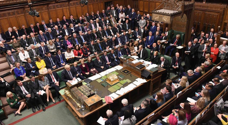 Britain's Prime Minister Boris Johnson, stands at left, to give a statement to lawmakers inside the House of Commons to update details of his new Brexit deal with EU, in London Saturday Oct. 19, 2019.