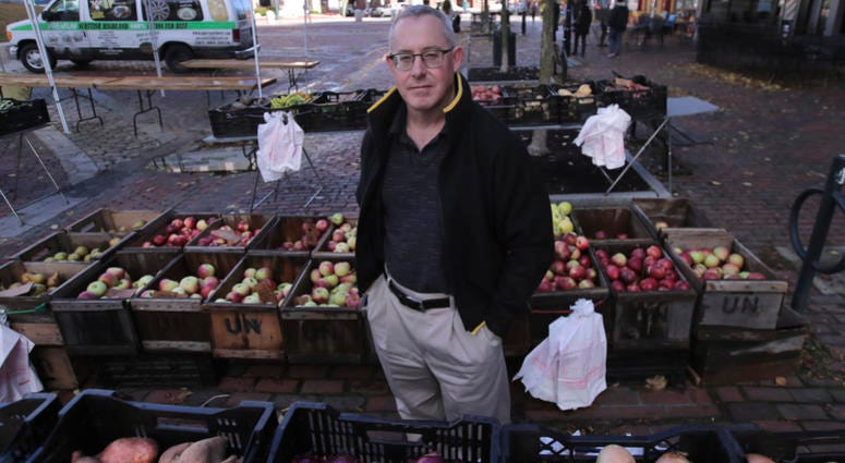 John Gold, self-employed graphics designer, poses at a farmer's market outside his office in Portland, Maine, Wednesday, Oct. 23, 2019.