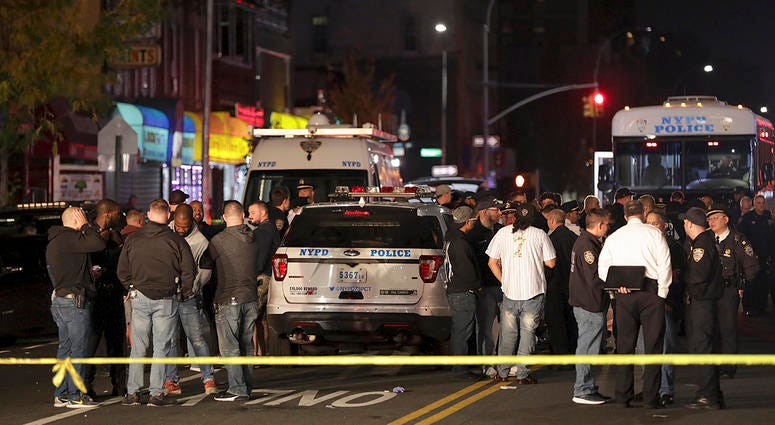 New York police and emergency personnel investigate the scene of a shooting at a Brooklyn nail salon. Police say the man who attacked a police officer with a metal chair was shot to death by the officer.