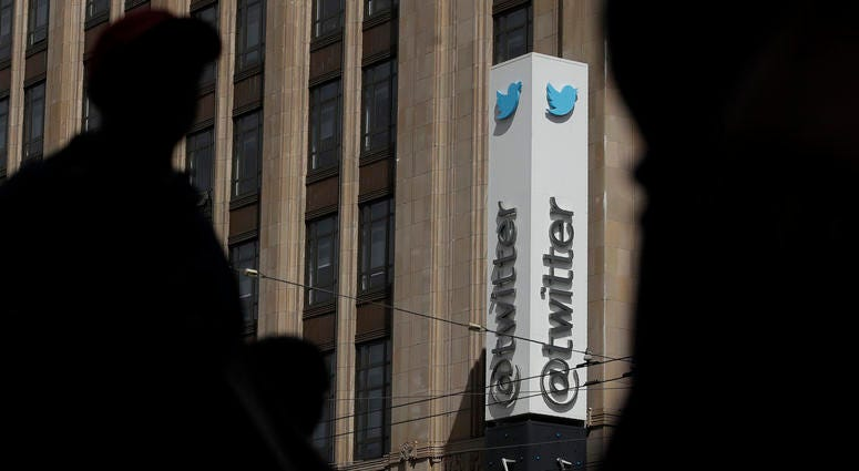 Pedestrians walk across the street from the Twitter office building in San Francisco.