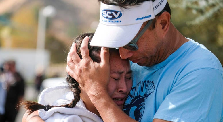 Ella Cabigting is embraced by her father Emerson as they reunite following a shooting at Saugus High School that injured several people, Thursday, Nov. 14, 2019, in Santa Clarita, Calif.