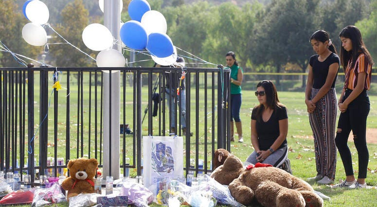 Parent Mirna Herrera kneels with her daughters Liliana, 15, and Alexandra, 16 at the Central Park memorial for the Saugus High School victims in Santa Clarita.