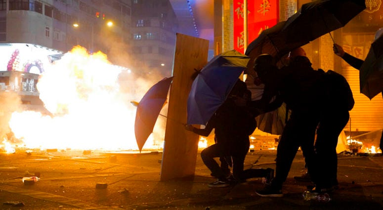 Protesters cover with umbrellas from tear gas canister in the Kowloon area of Hong Kong, Monday, Nov. 18, 2019.