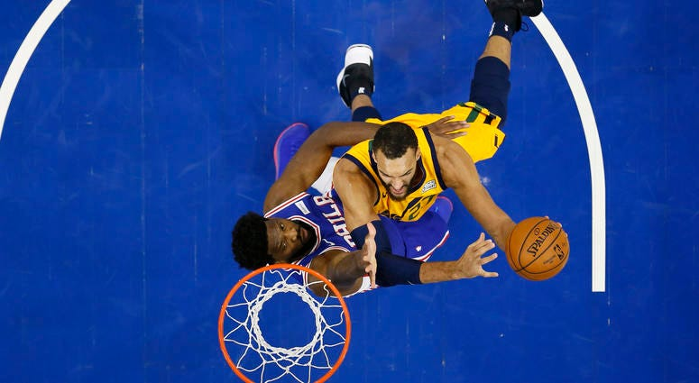 Utah Jazz's Rudy Gobert, right, goes up to shoot against Philadelphia 76ers' Joel Embiid during the first half of an NBA basketball game, Monday, Dec. 2, 2019, in Philadelphia.