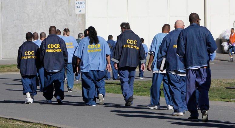 Inmates walk through the exercise yard at California State Prison Sacramento, near Folsom, Calif., on Feb. 26, 2013.