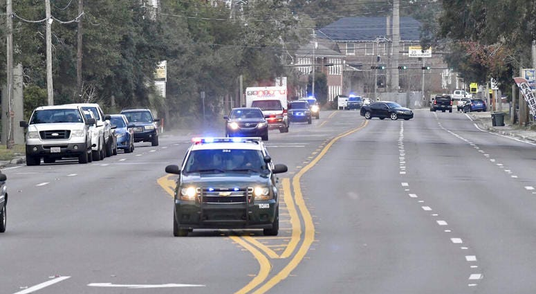 Police cars escort an ambulance after a shooter open fire inside the Pensacola Air Base, Friday, Dec. 6, 2019 in Pensacola, Fla.