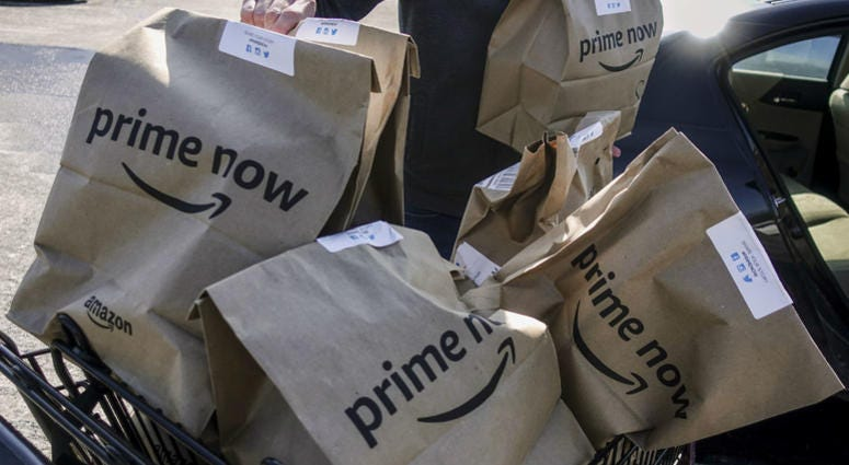 In this Feb. 8, 2018, file photo, Amazon Prime Now bags full of groceries are loaded for delivery by a part-time worker outside a Whole Foods store in Cincinnati.