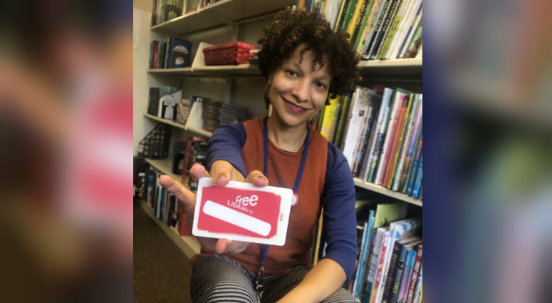 Jamie Bowers, electronic resources coordinator for the Free Library of Philadelphia, shows off the library card, your passport to the Experience Pass program.