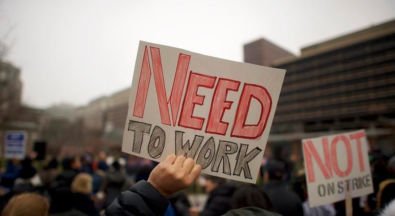 """Fred Jennings, 67, holds a placard stating """"NEED TO WORK"""" while gathering with area elected officials and furloughed federal workers at a rally in front of Independence Hall on Jan. 8, 2019 in Philadelphia, Pennsylvania."""