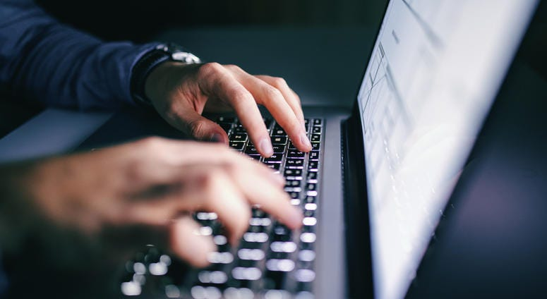 Close up of hands typing on laptop.