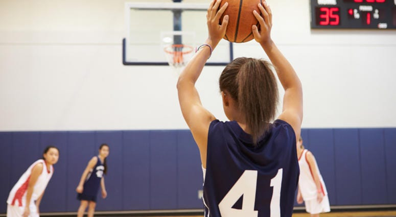 A group of girls playing basketball.