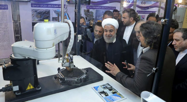 """President Hassan Rouhani listens to explanations on new nuclear achievements at a ceremony to mark """"National Nuclear Day,"""" in Tehran, Iran."""