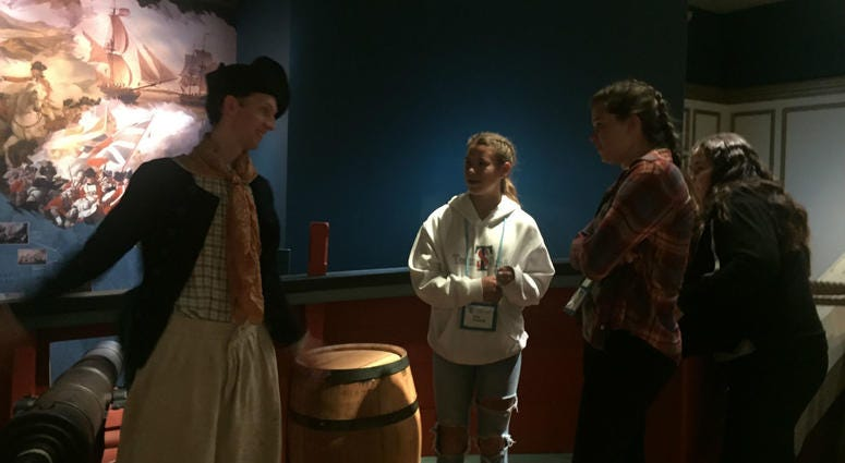 A historical interpreter talks to visitors at the American Revolution Museum.