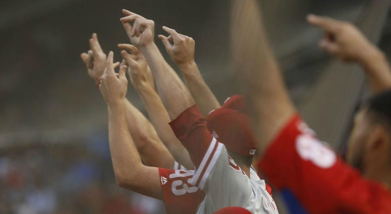 The Philadelphia Phillies snap their fingers as a run scores against the Boston Red Sox in the second inning at Fenway Park.