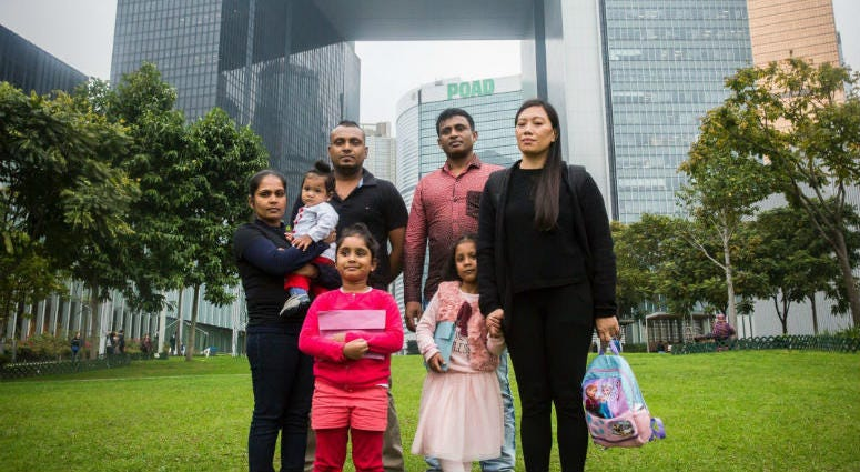 Sri Lankan refugee Supun Thilina Kellapatha (third from left), his partner Nadeeka (left), with their baby boy Dinath, daughter Sethumdi, Sri Lankan refugee Ajith Puspa (third from right),and Filipino refugee Vanessa Rodel (right) with her daughter Keana