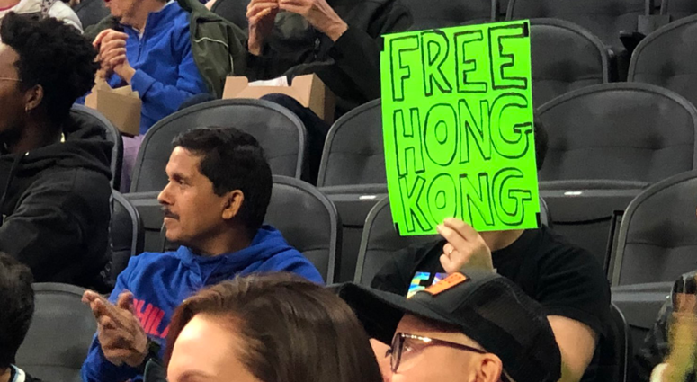 "Sam Wachs is shown holding a sign reading ""Free Hong Kong."""