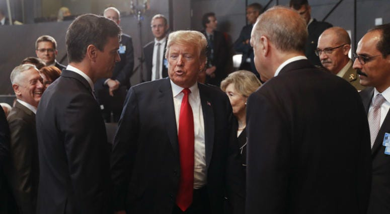President Donald Trump, center, stops to talk with Spanish Prime Minister Pedro Sanchez, left, and Turkey's President Recep Tayyip Erdogan, right, as they attend a meeting of the North Atlantic Council.