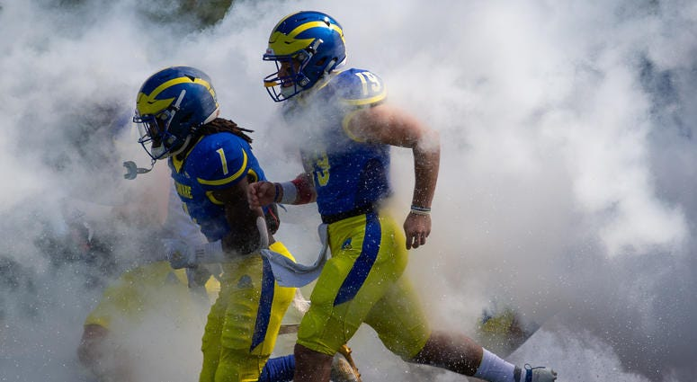 Members of the University of Delaware Blue Hens running onto the football field.