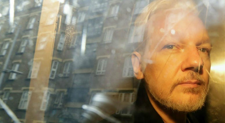 In this Wednesday May 1, 2019 file photo, buildings are reflected in the window as WikiLeaks founder Julian Assange is taken from court, where he appeared on charges of jumping British bail seven years ago, in London.