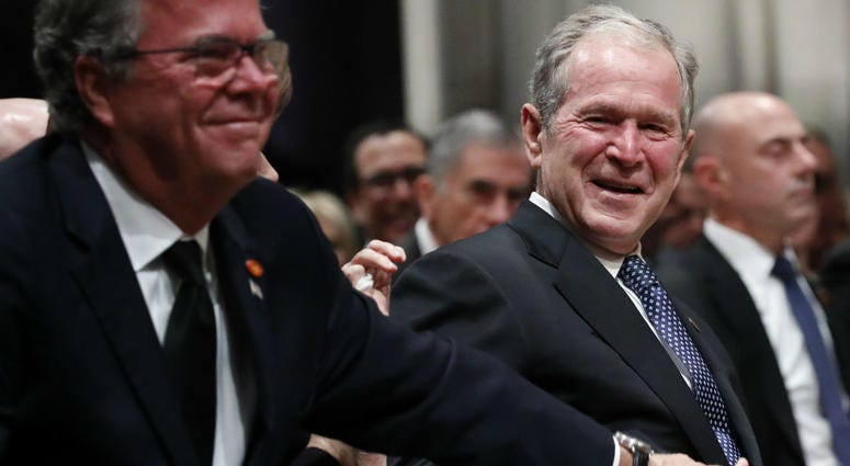 Former President George W. Bush smiles with his brother Jeb Bush at the state funeral for their father, former President George H.W. Bush, at the Washington National Cathedral on December 5, 2018 in Washington, DC.