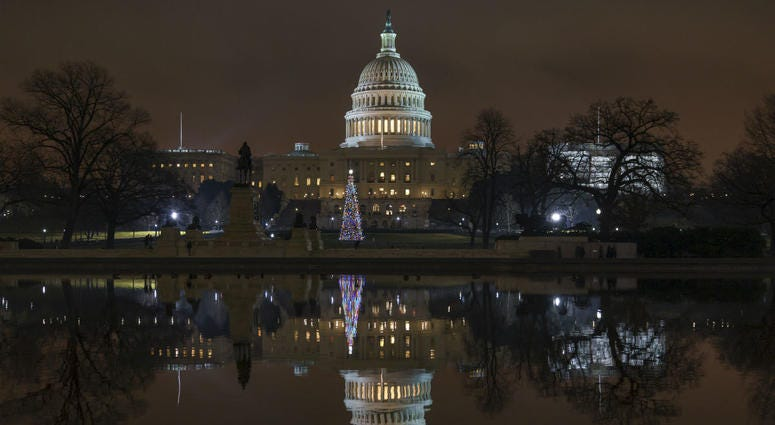 The Capitol is mirrored in the Reflecting Pool in Washington, as a partial government shutdown heads into a second week, Friday night, Dec. 28, 2018.