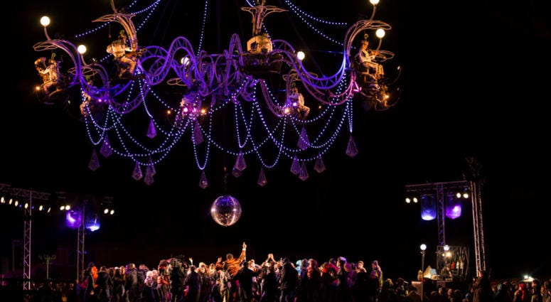 The musicians of the French troupe Transe Express play instruments on a steel chandelier.