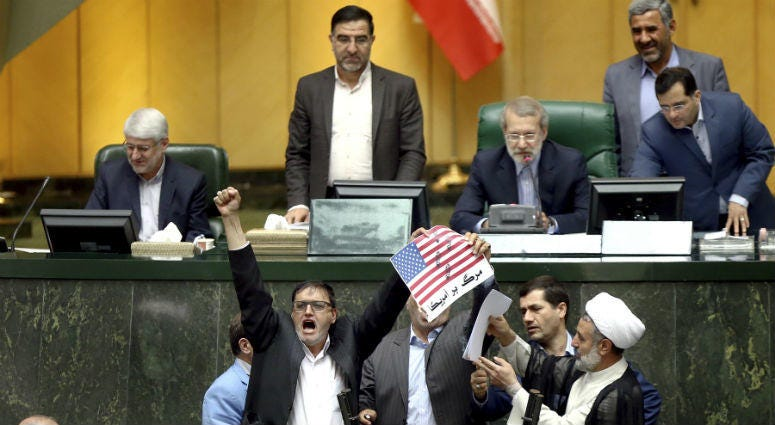 Iranian lawmakers burn two pieces of papers representing the U.S. flag and the nuclear deal as they chant slogans against the U.S. at the parliament in Tehran, Iran, Wednesday, May 9, 2018.