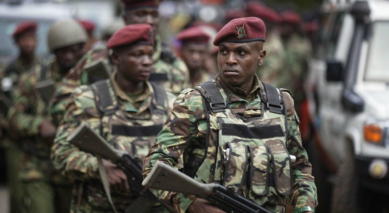 Kenyan security forces walk from the scene as continued blasts and gunfire could be heard early Wednesday, Jan. 16, 2019, in Nairobi, Kenya.