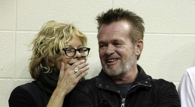 In this Dec. 31, 2011 file photo, Actress Meg Ryan, left, talks with performer John Mellencamp during the second half of an NCAA college basketball game between Indiana and Ohio State in Bloomington, Ind.