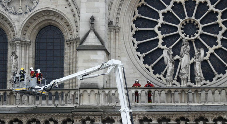 Firefighters work at the facade of Notre Dame cathedral Tuesday April 16, 2019 in Paris.