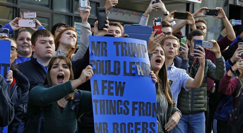 University of Pittsburgh sophomore Lynne Jaworski, from Homer City, Pa., holds a sign and yells as President Donald Trump's motorcade arrives at the University of Pittsburgh's Presbyterian Hospital.